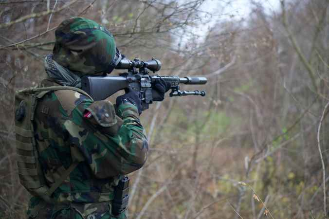 man in camouflage army uniform holding rifle