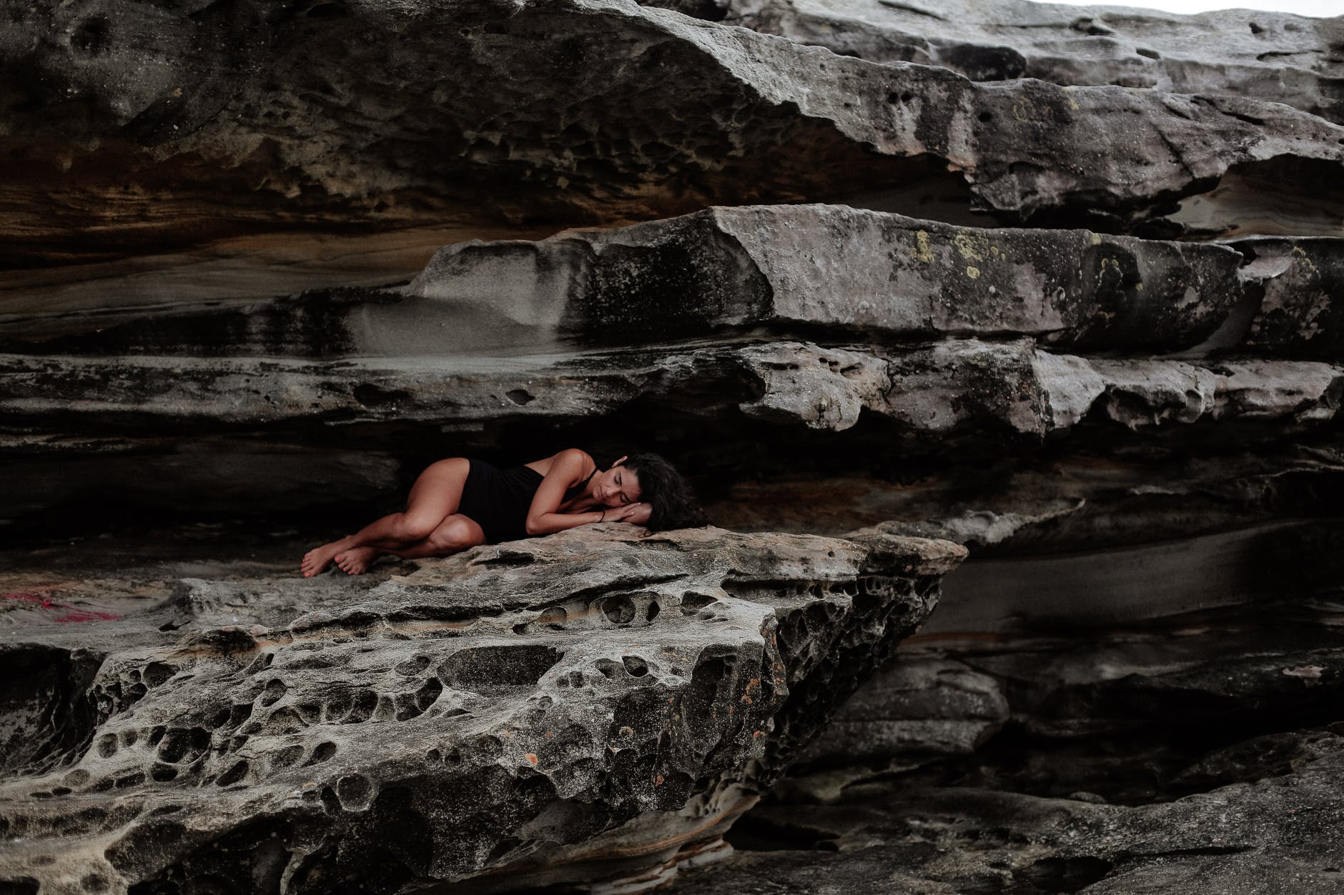 woman lying on rock