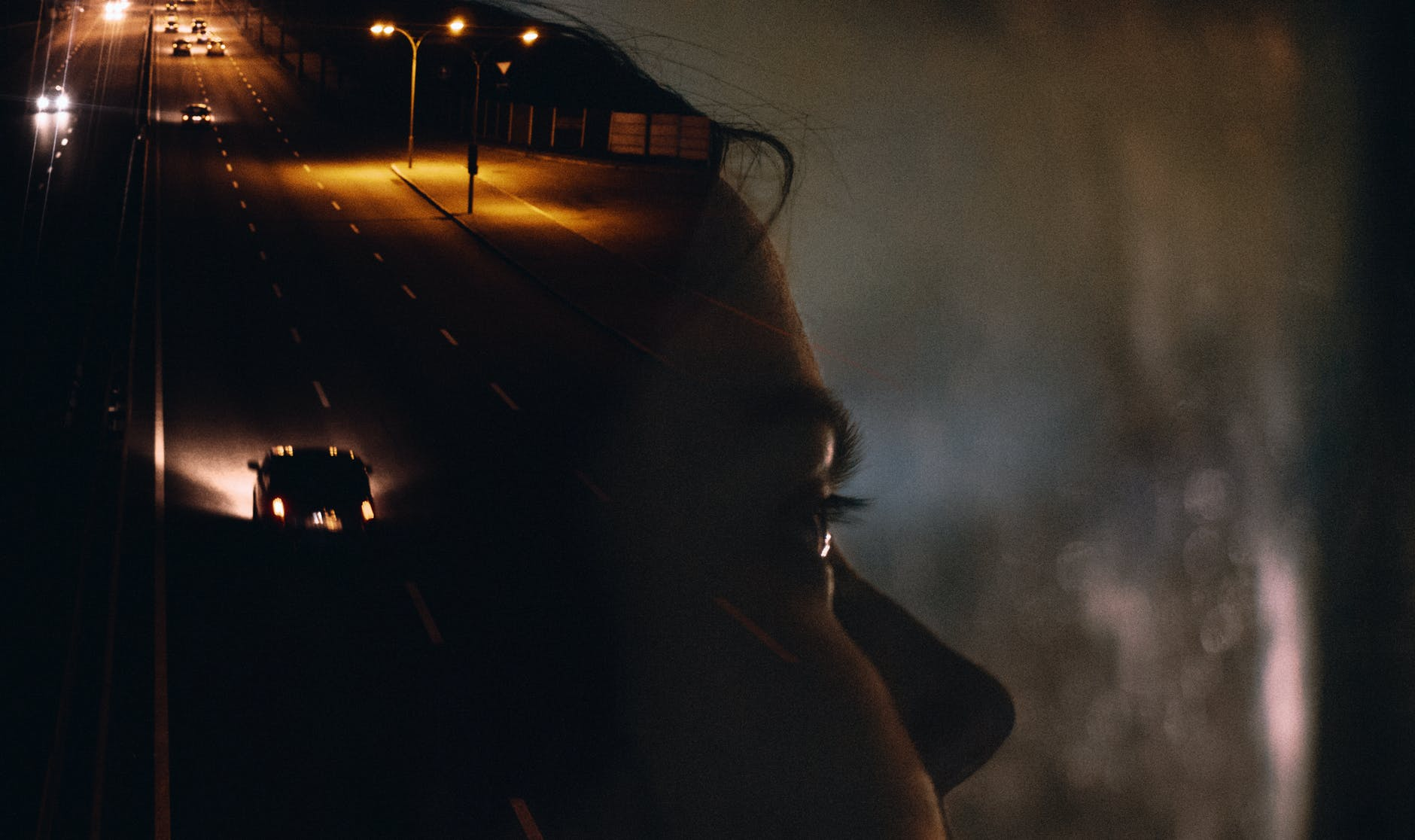 woman in car with road reflection on window at night